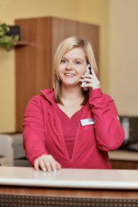 Arzthelferin Julia telefoniert mit Patienten.